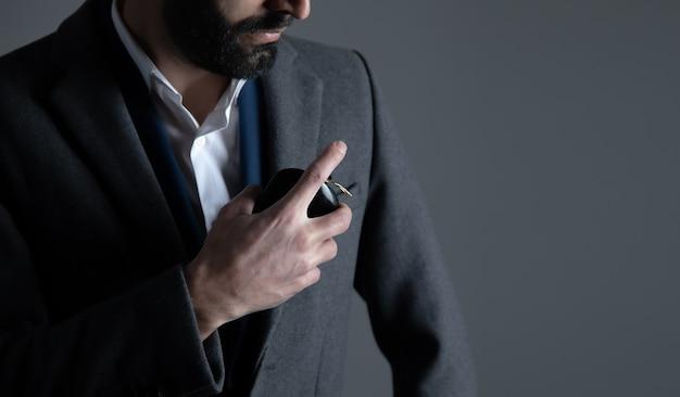 Mão de homem segurando frasco de perfume