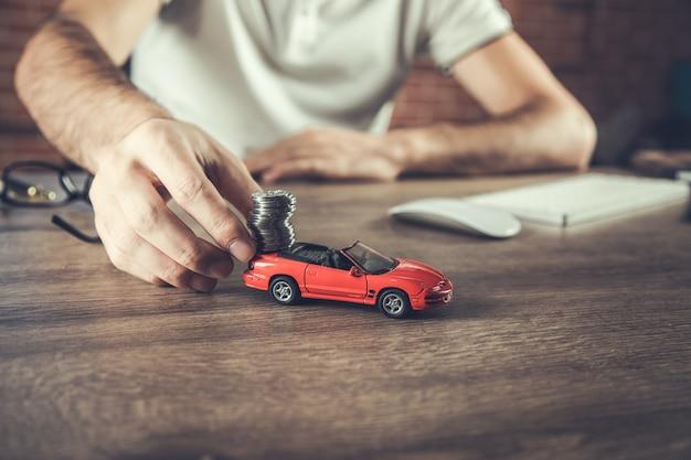 Mão de homem segurando modelo de carro e moedas