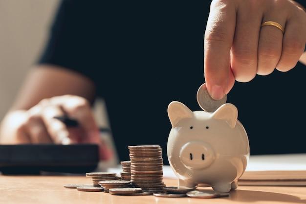 Mão de homem segurando moedas, colocando no cofrinho, economizando dinheiro e investindo conceito de economia de dinheiro para contabilidade financeira