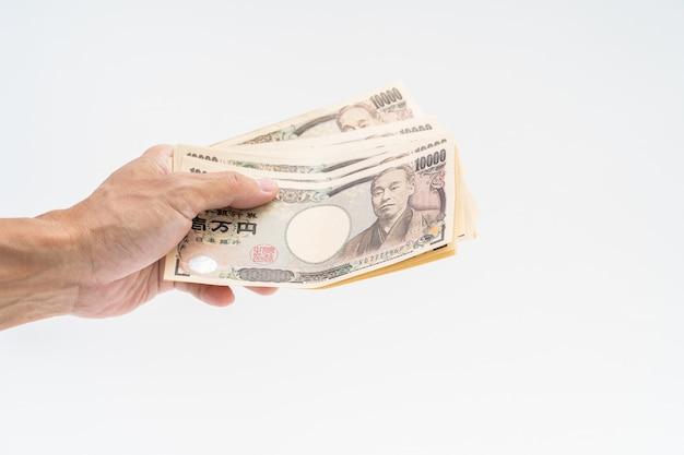 Mão de homem segurando notas japonesas em fundo branco