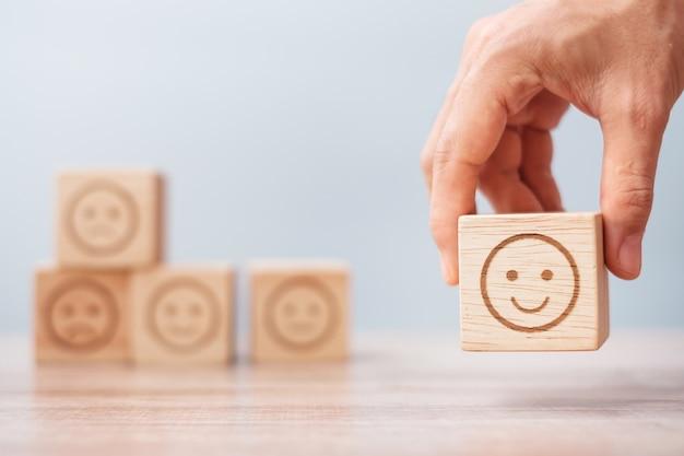 Mão de homem segurando o bloco de rosto de emoção. o cliente escolhe o emoticon para as análises dos usuários. classificação do serviço, classificação, revisão do cliente, satisfação, avaliação e conceito de feedback