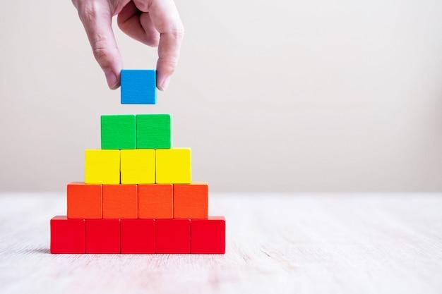 Mão de homem segurando o bloco do cubo de cor azul, construindo uma pirâmide