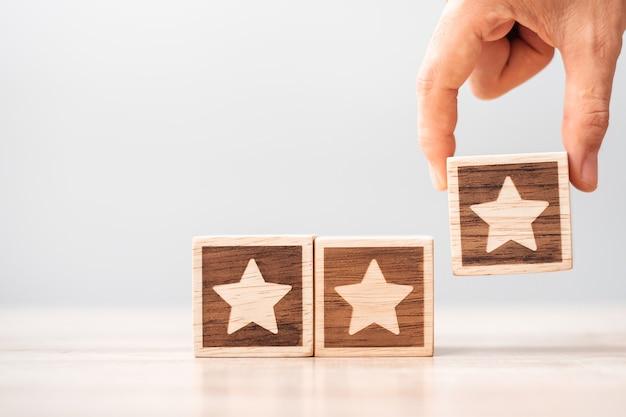 Mão de homem segurando o bloco estrela. o cliente escolhe a classificação para comentários do usuário. classificação do serviço, classificação, revisão do cliente, satisfação, avaliação e conceito de feedback