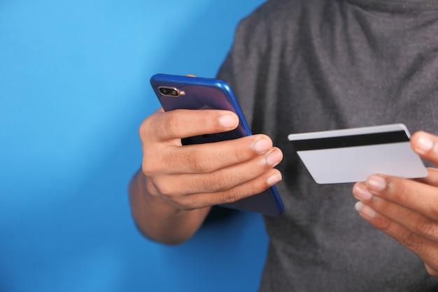 Mão de homem segurando o cartão de crédito e usando o telefone inteligente, compras online.