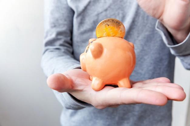 Mão de homem segurando o cofrinho com dinheiro virtual eletrônico de moeda de ouro bitcoin criptomoeda para banco na web e pagamento em rede internacional
