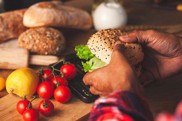 Mão de homem segurando o delicioso hambúrguer caseiro com legumes frescos