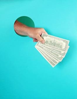 Mão de homem segurando o dinheiro sobre o papel azul.
