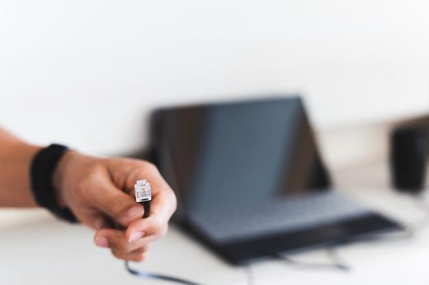 Mão de homem segurando o fio do cabo de internet com o laptop no fundo.