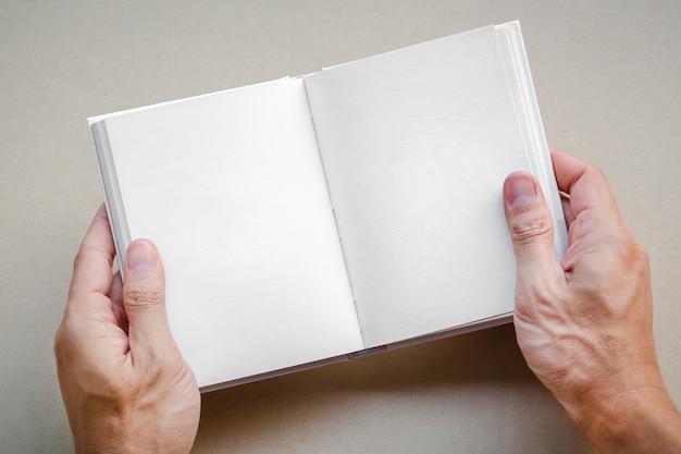 Mão de homem segurando o livro aberto em branco simulado acima