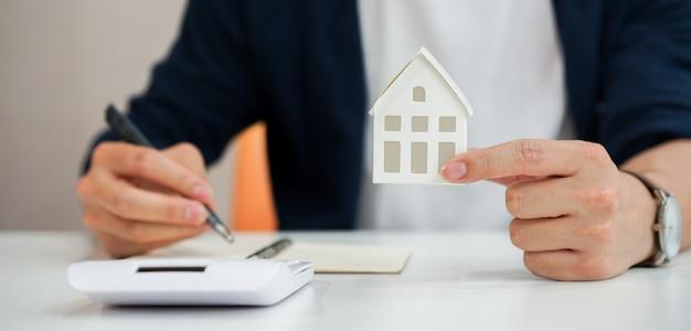 Mão de homem segurando o modelo da casa e escrever a despesa resumida da hipoteca de empréstimo à habitação para refinanciar o plano