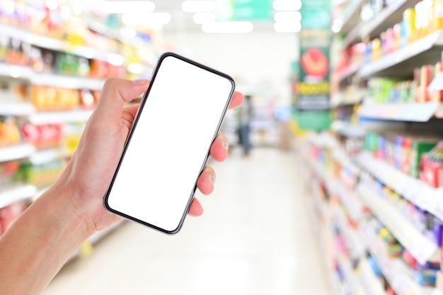 Mão de homem segurando o smartphone de tela em branco no supermercado