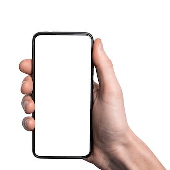Mão de homem segurando o smartphone preto com quadro menos tela em branco e design moderno sem moldura, vertical - isolado na superfície branca. caminho de recorte. interface de design de ii.