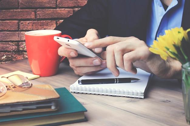 Mão de homem segurando o telefone com o caderno de papel e a xícara de café na mesa de madeira