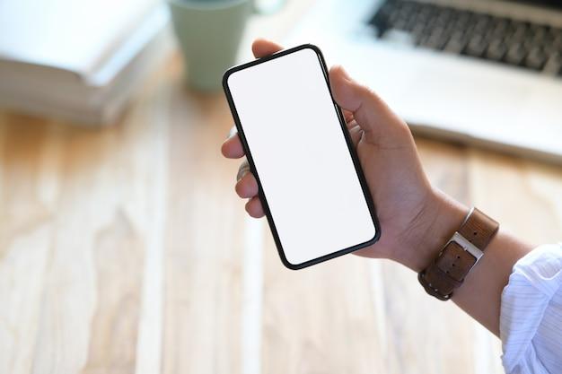 Mão de homem segurando o telefone inteligente móvel com tela em branco