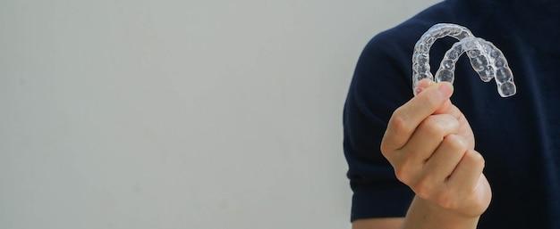 Mão de homem segurando retentor alinhador dentário