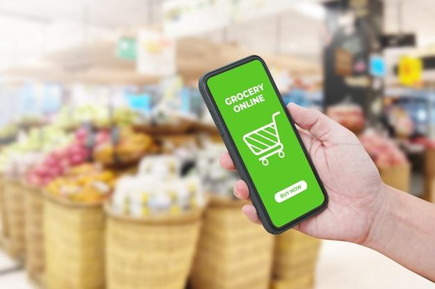 Mão de homem segurando smartphone contra desfocar bokeh de plano de fundo da loja. supermercado online.