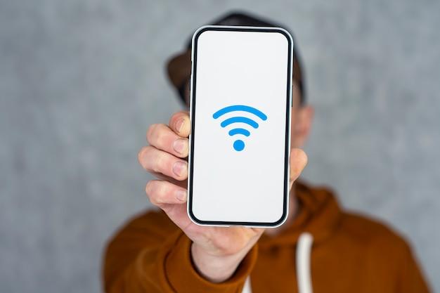 Mão de homem segurando smartphone prata isolado na luz de fundo. maquete de telefone com tela branca e ícone de wi-fi.
