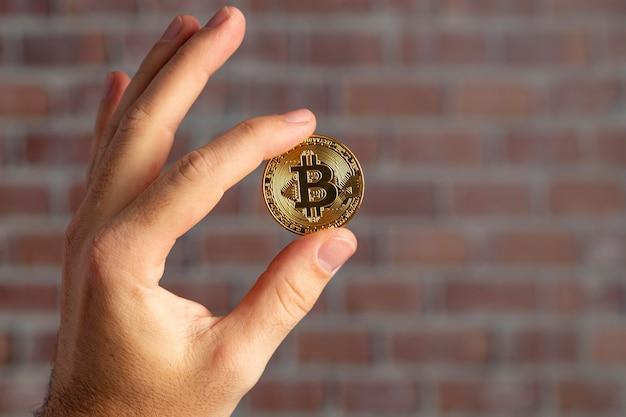 Mão de homem segurando um bitcoin físico em frente a uma parede de tijolos