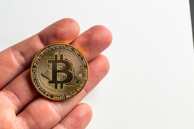 Mão de homem segurando um bitcoin físico na frente de uma superfície branca