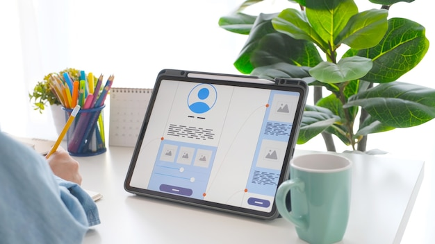 Mão de homem segurando um lápis e um tablet digital com protótipo de desenvolvimento de aplicativo móvel na tela enquanto trabalha em casa