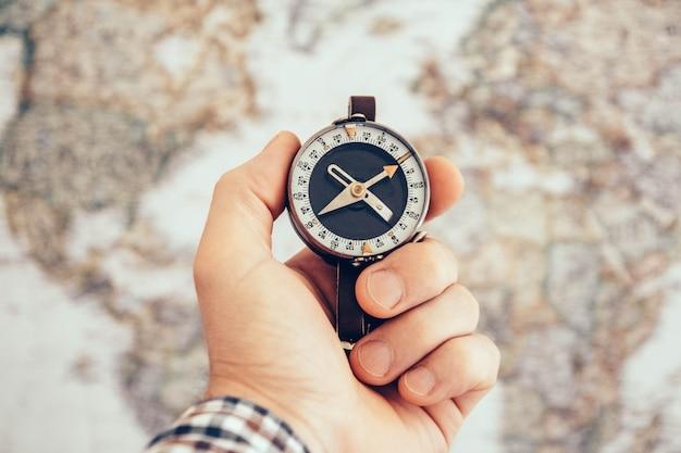 Mão de homem segurando uma bússola vintage com mapa-múndi como pano de fundo