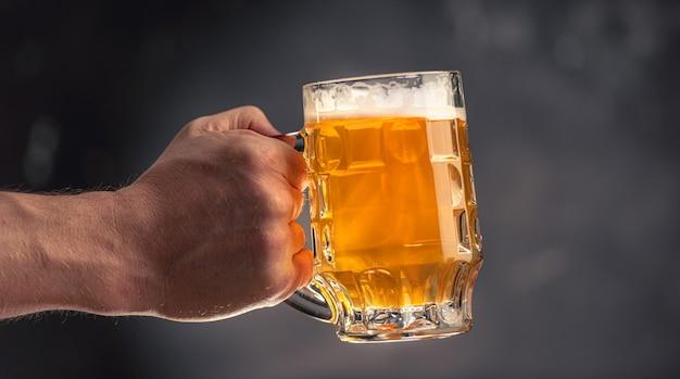 Mão de homem segurando uma caneca cheia de cerveja light isolada em fundo cinza escuro