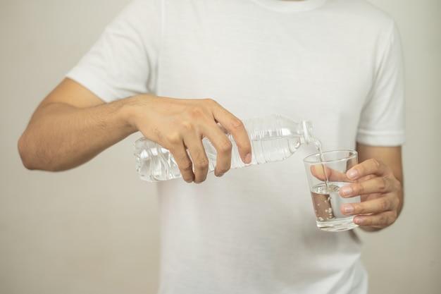 Mão de homem segurando uma garrafa de água derramando água em um copo.