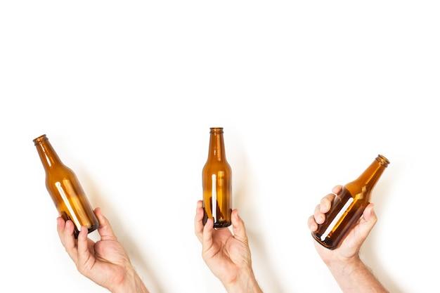 Mão de homem segurando uma garrafa de cerveja vazia