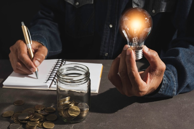 Mão de homem segurando uma lâmpada e copie o espaço para contabilidade