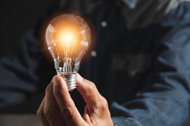 Mão de homem segurando uma lâmpada e copie o espaço
