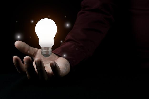 Mão de homem segurando uma lâmpada