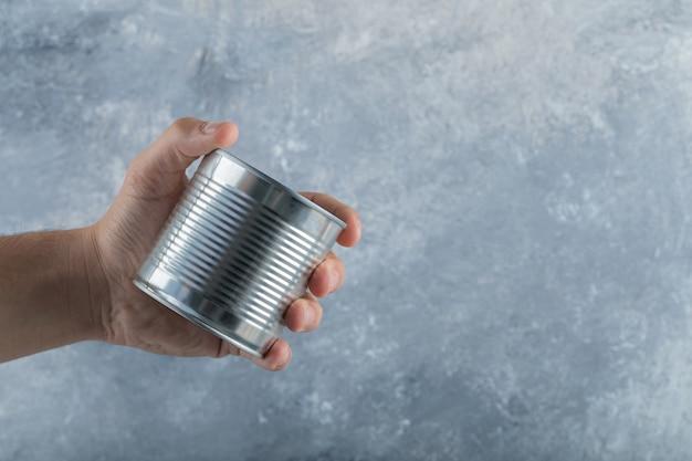 Mão de homem segurando uma lata metálica no mármore.