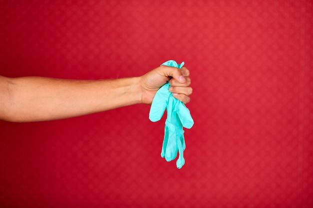 Mão de homem segurando uma luva de proteção médica de látex azul sobre fundo vermelho do estúdio, equipamento de proteção contra coronavírus durante a pandemia de covid-19