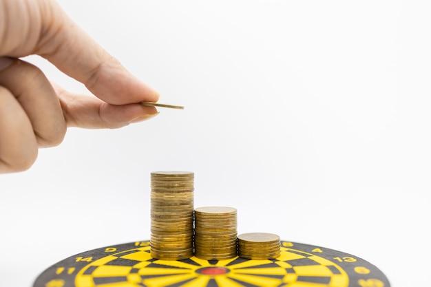 Mão de homem segurando uma moeda e colocando no topo da pilha de moedas no tabuleiro de dardo.