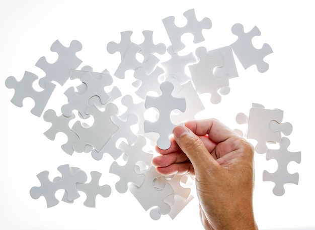 Mão de homem segurando uma peça do quebra-cabeça