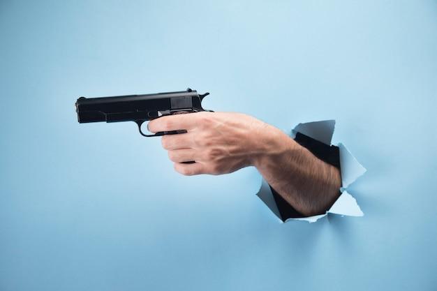 Mão de homem segurando uma pistola em uma cena azul