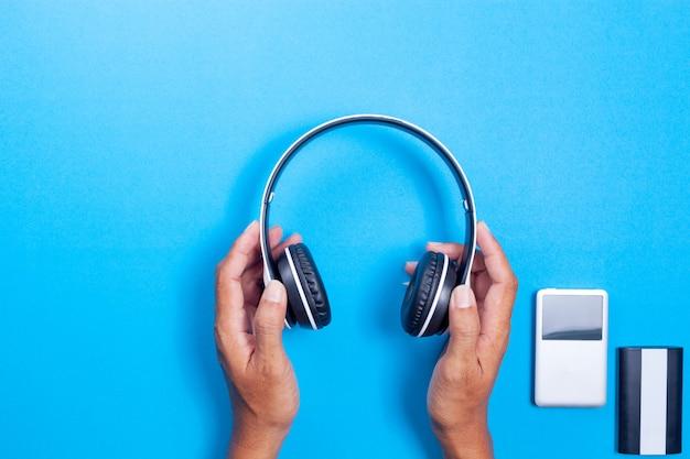Mão de homem segurar fone de ouvido sem fio, media player, banco de potência em fundo de papel azul