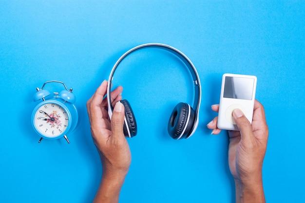 Mão de homem segurar fone de ouvido sem fio, media player, despertador azul sobre fundo de papel azul