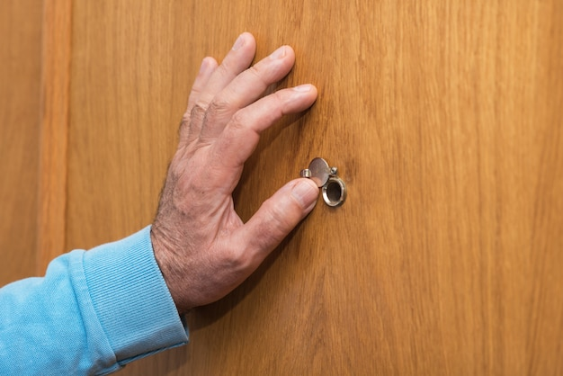 Mão de homem sênior abrir a porta da tampa do olho mágico