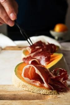 Mão de homem servindo, experimentando, degustando, organizando as tradicionais tapas espanholas jamon iberico com melão e manjericão sobre tábua de mármore.