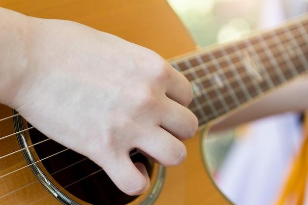 Mão de homem tocando violão, conceito musical