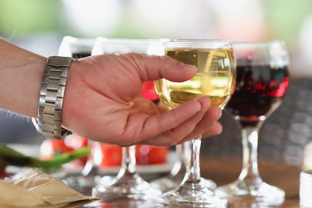 Mão de homem tomando um copo de vinho branco em close up do restaurante