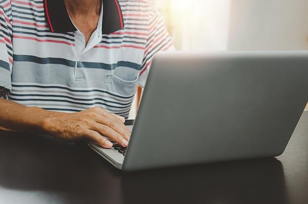 Mão de homem usando computador portátil na mesa em casa, pesquisando informações, navegar na internet na web, trabalhar em casa. conceito de negócio