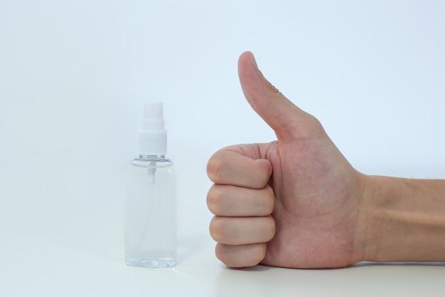 Mão de homem usando dispensador de bomba de desinfetante de mão de lavagem para proteção contra coronavírus. conceito de cuidados de saúde, covid 19. feche o polegar para cima desinfetante para as mãos - como ou aprove o sinal na parede branca com espaço de cópia