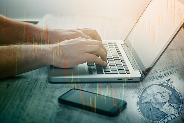 Mão de homem usando laptop de negociação de moedas e ações na bolsa forex. gráfico de bastão de vela e gráfico de barras do mercado de ações. conceito de investir dinheiro e obter lucro.