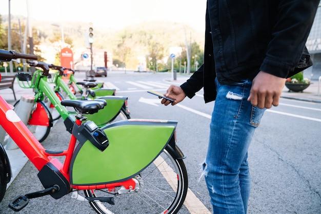 Mão de homem usando o celular para pegar uma bicicleta elétrica alugada no parque de bicicletas na rua