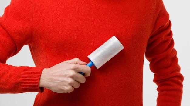 Mão de homem usando removedor de fiapos para limpar tecidos