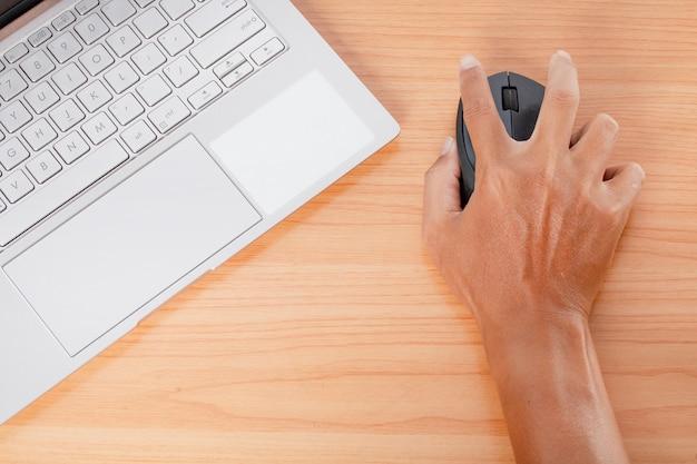 Mão de homem usando um laptop na mesa