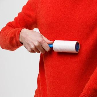 Mão de homem usando um rolo pegajoso para limpar tecidos