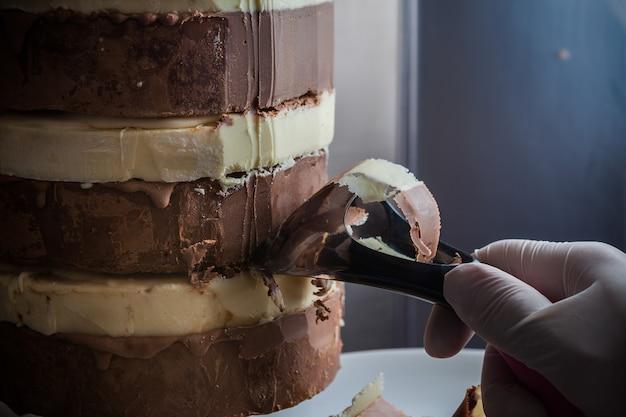 Mão de homem vista lateral, corte o chocolate preto e branco no prato